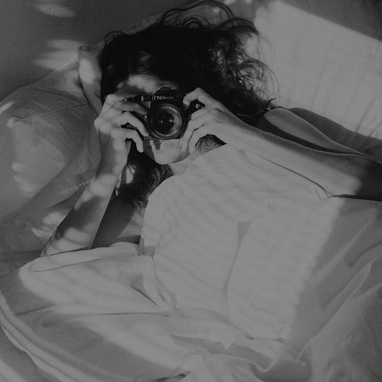 Woman in bed with a camera